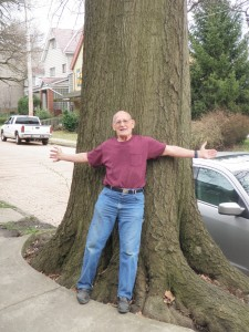 Larry stands with an oak tree, one of the largest oldest trees in the borough of Wilkinsburg.