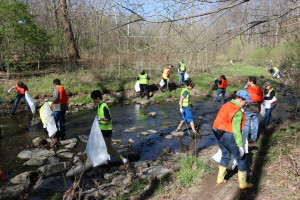 Volunteers picking trash out of Nine Mile Run stream.